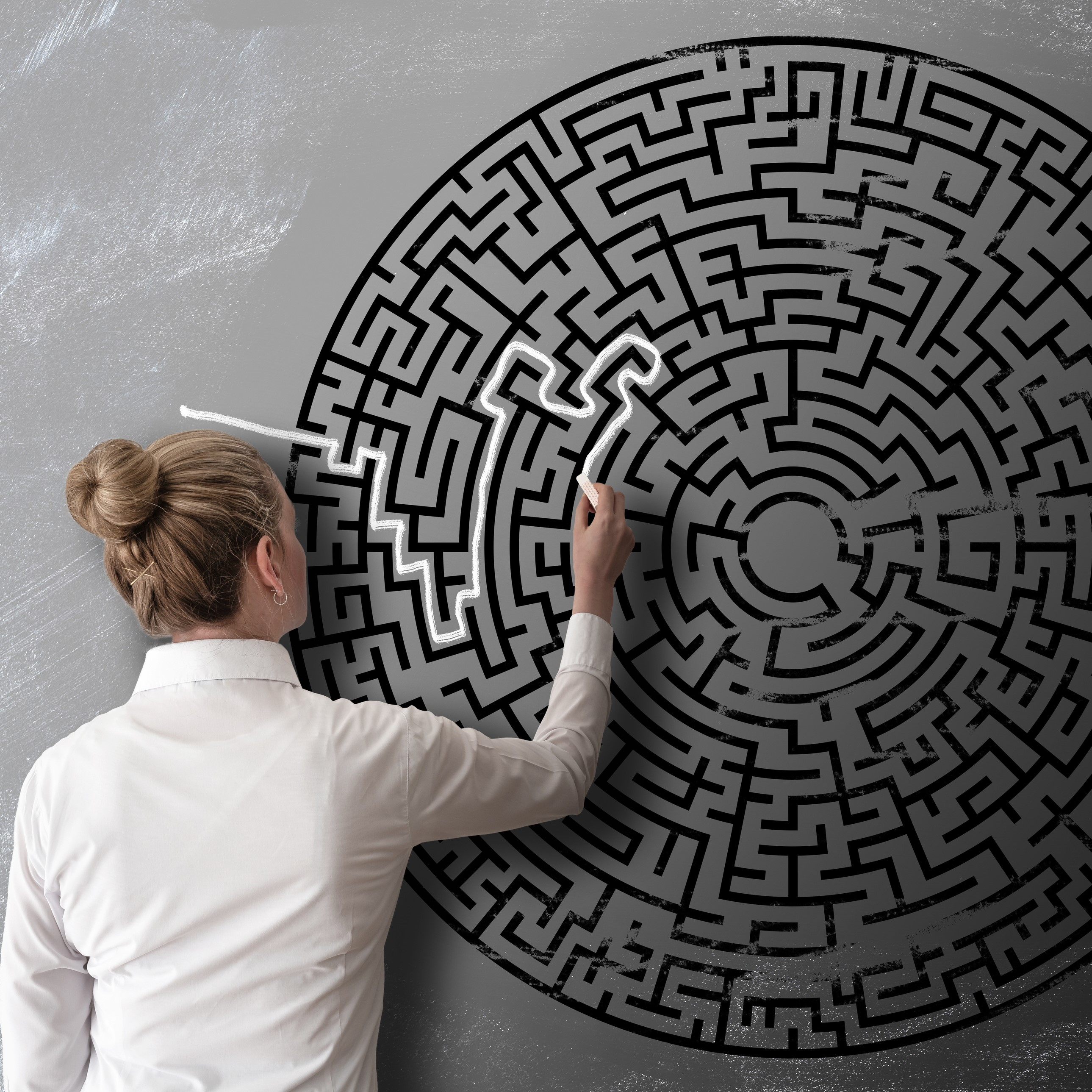 Woman Trying To Find Way Through Chalk Drawing Of Maze On Blackboard